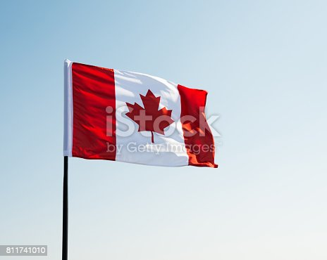 istock Canadian flag waving  against clear blue sky 811741010