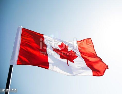 istock Canadian flag waving  against clear blue sky 811741012
