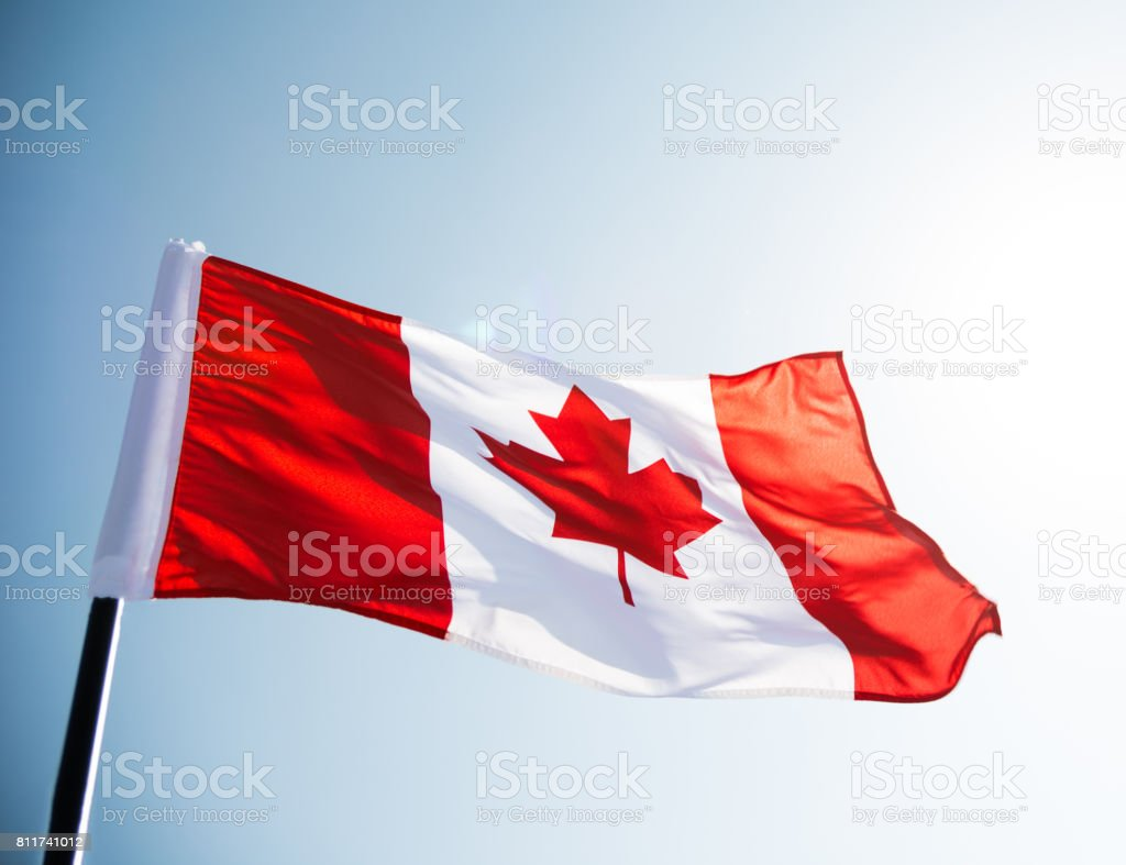 Agitar contra el cielo azul de la bandera de Canadá - foto de stock