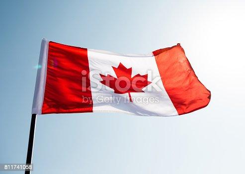 istock Canadian flag waving  against clear blue sky 811741058
