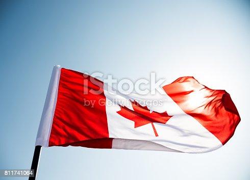 istock Canadian flag waving  against clear blue sky 811741064
