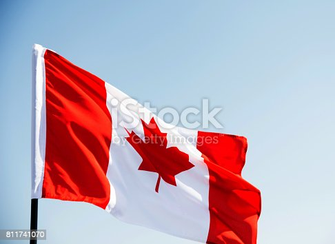 istock Canadian flag waving  against clear blue sky 811741070