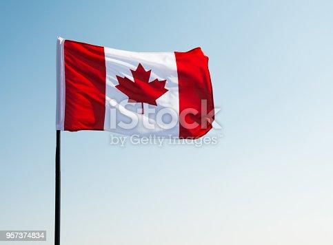 istock Canadian flag waving  against clear blue sky 957374834