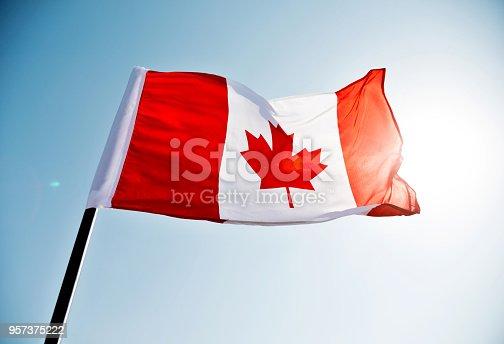 istock Canadian flag waving  against clear blue sky 957375222