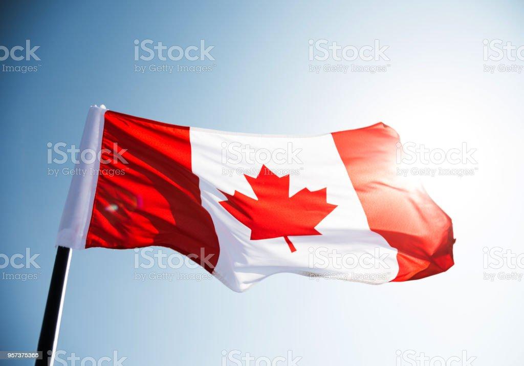 Kanadische Flagge winken gegen blauen Himmel – Foto