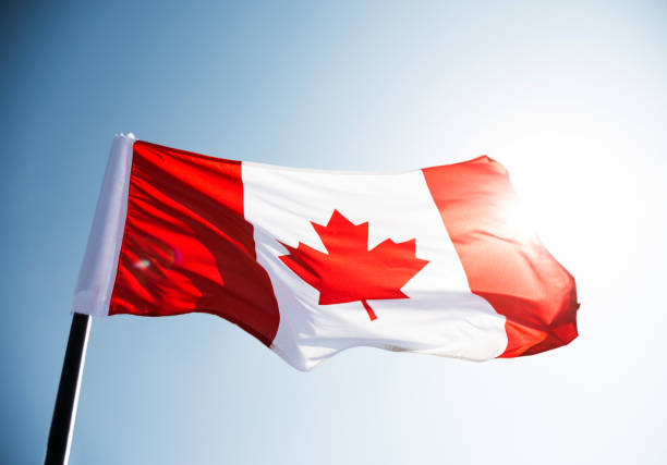 canadian flag waving  against clear blue sky - canada day stock pictures, royalty-free photos & images