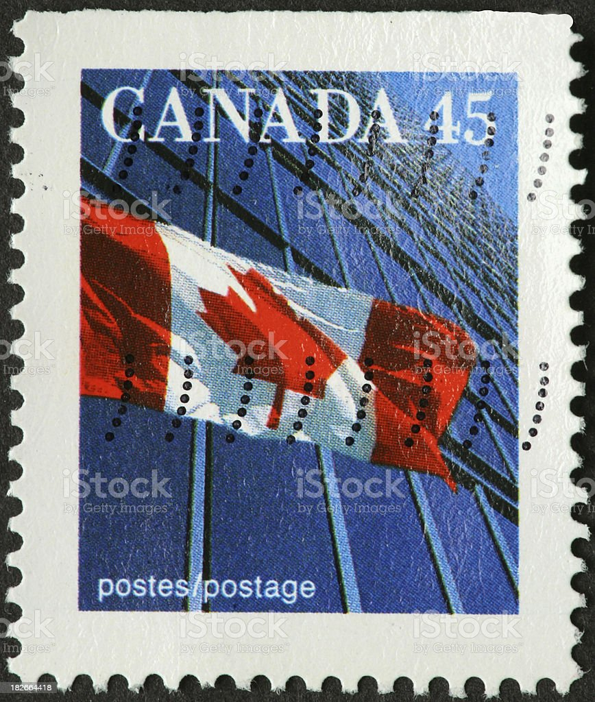 Canadian flag waving in front of a skyscraper stock photo