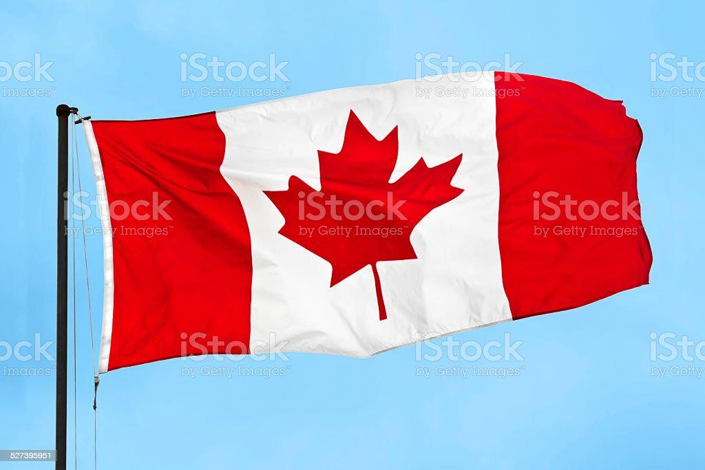 Bandera canadiense Saludar con la mano en el viento en contra el cielo azul - foto de stock