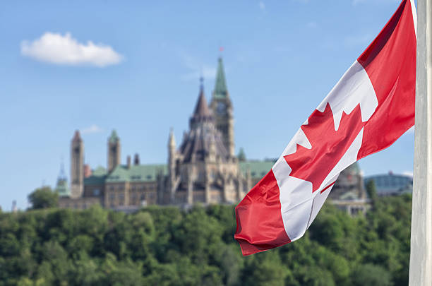 canadian flag waving with parliament buildings hill and library - canada stockfoto's en -beelden
