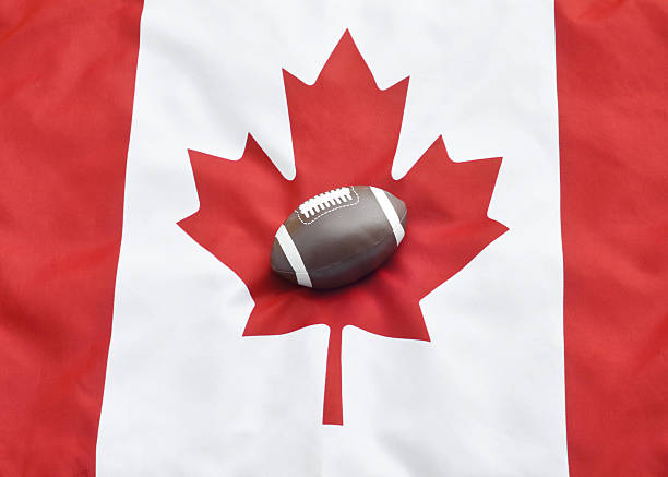 Canadian Football Close up of a toy football on a Canadian flag symbolizing Canadian Football. canadian football league stock pictures, royalty-free photos & images