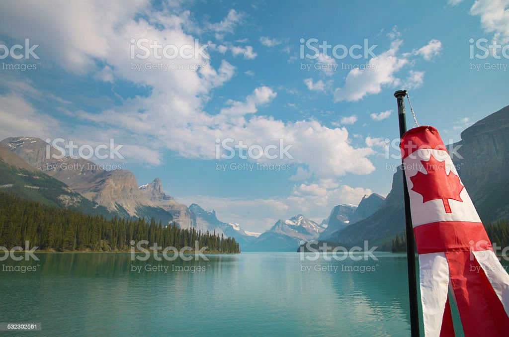 Canadian landscape with mountains, Maligne lake and flag. Albert stock photo