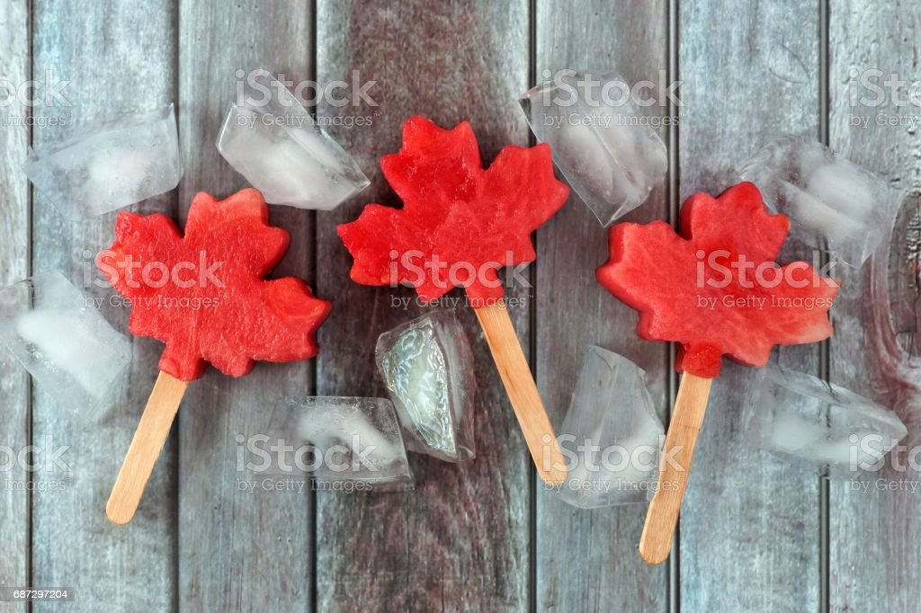 Canadian maple leaf watermelon pops on rustic wood stock photo