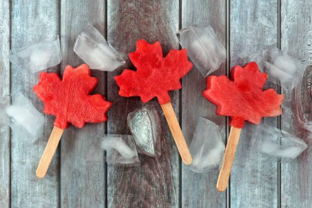 canadian maple leaf watermelon pops on rustic wood - canada day stock pictures, royalty-free photos & images