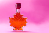 Canadian maple syrup in maple leaf shaped glass bottle, isolated on pink background
