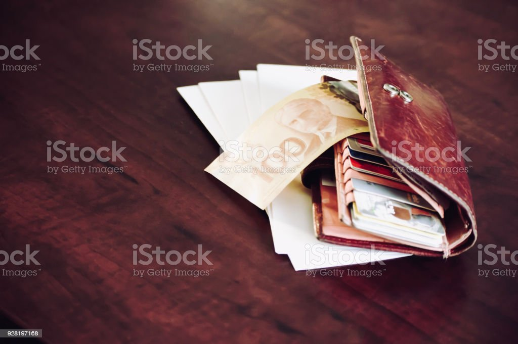 Canadian Money in wallet on table with credit and debit cards and cash with envelopes stock photo