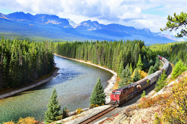Canadian Pacific Railway in Banff National Park,Canada. Long freight train Canadian Pacific Railway (CPR) moving along Bow river in Canadian Rockies ,Banff National Park, Canadian Rockies,Canada. canadian rockies stock pictures, royalty-free photos & images