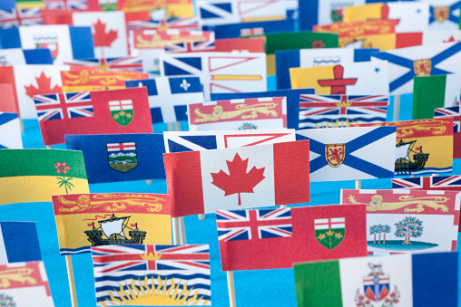 Paper made flag of canadian provinces and territories over blue background