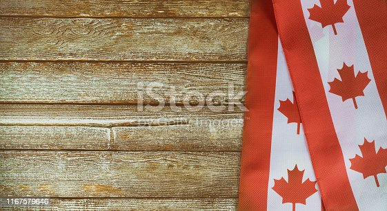 istock Canadian red and white flag against dark rustic background for Canada Day celebration and national holidays 1167579646