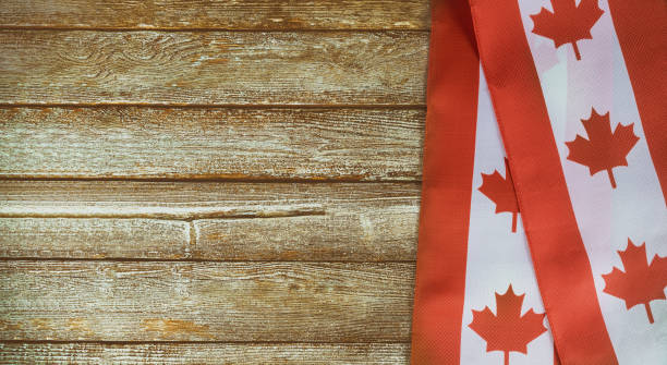 canadian red and white flag against dark rustic background for canada day celebration and national holidays - canada day stock pictures, royalty-free photos & images