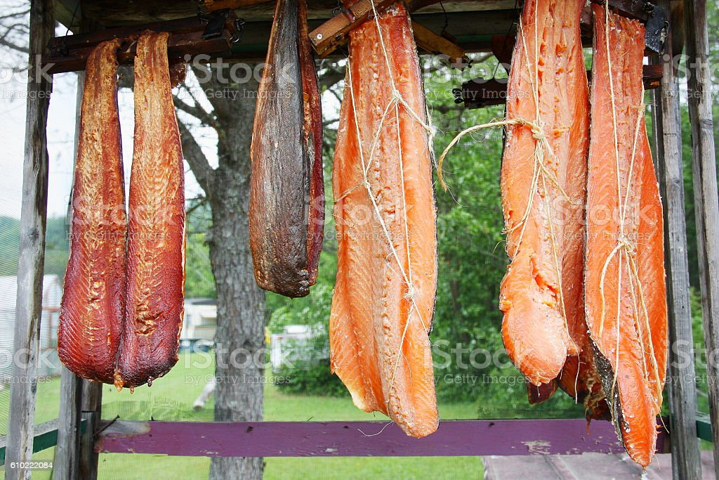 Canadian red salmon strips hung to smoke on rack outdoor stock photo