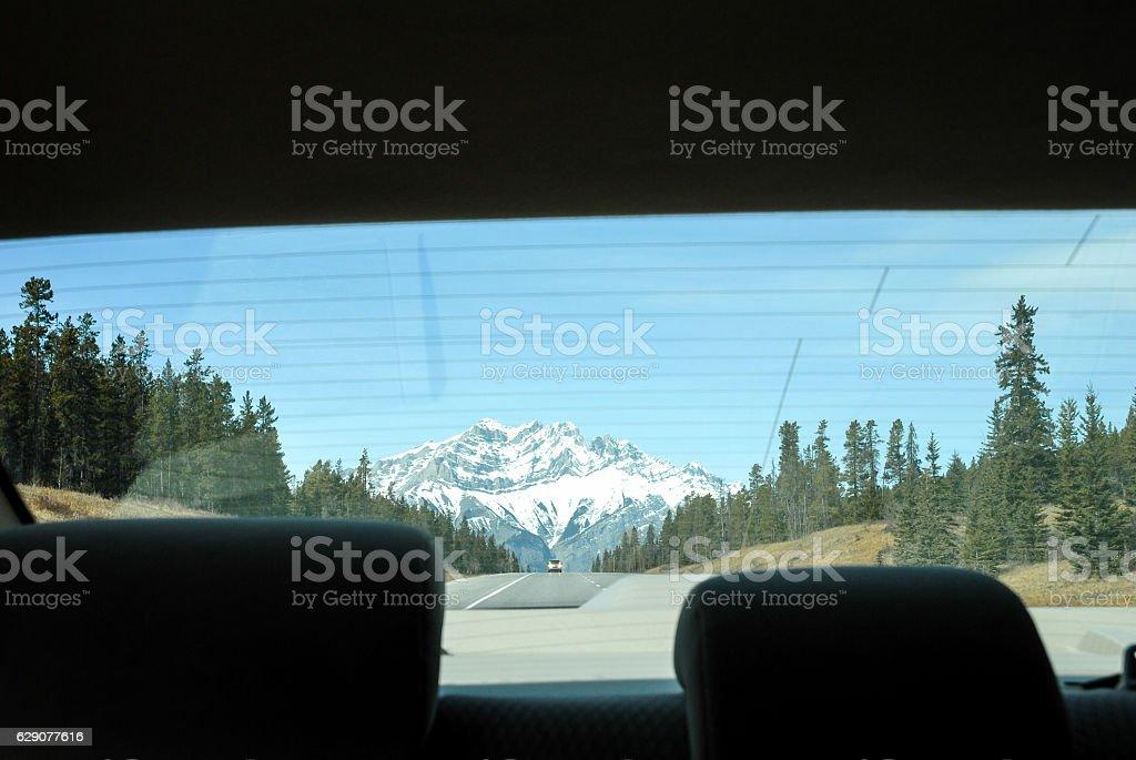 Canadian Rockies Going Away through Rear Window of a Car – Foto
