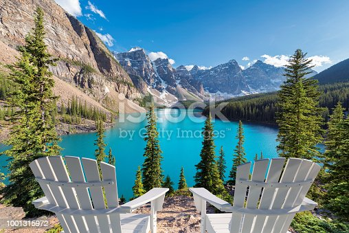 Two chairs near beautiful turquoise waters of the Moraine Lake at sunset with snow-covered peaks above it in Rocky Mountains, Banff National Park, Canada.