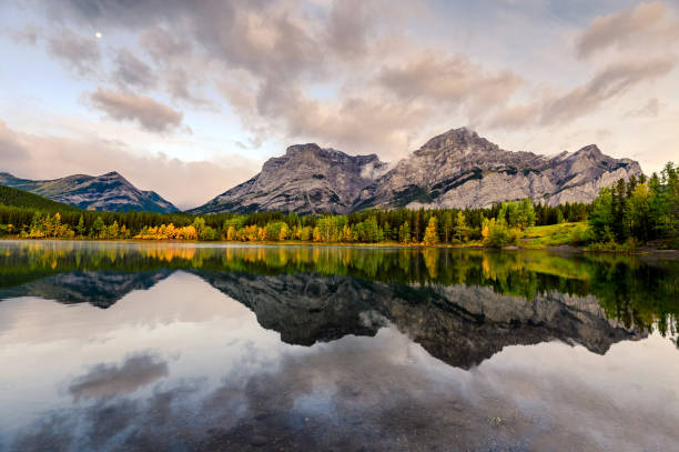 Canadian rockies with the moon reflection on Wedge pond in the morning at Kananaskis country Canadian rockies with the moon reflection on Wedge pond in the morning at Kananaskis country, Canada kananaskis country stock pictures, royalty-free photos & images