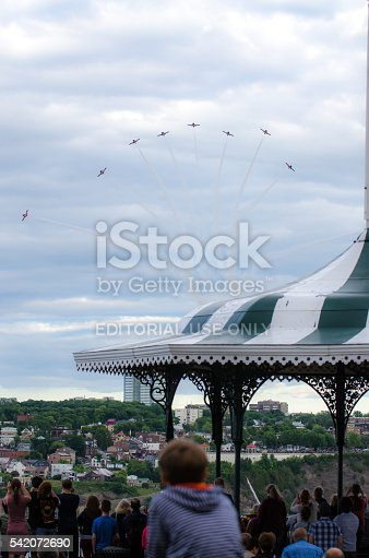 Quebec, Canada - June 15, 2016: Nine Canadian Snowbirds aircraft flying towards the crowd on Terrace Dufferin with a Canadian Flag on a gazebo during day of summer