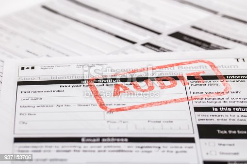 A stock photo of the Canadian T1 General Tax forms. Showing a red ink stamp with the word