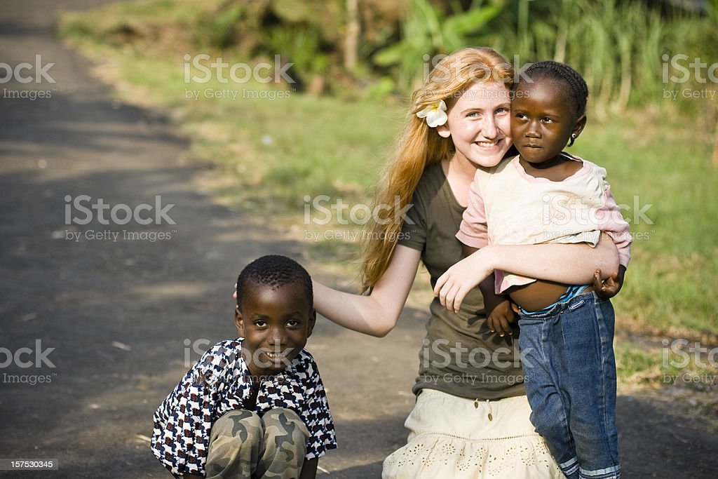Canadian teen holding two needy African children royalty-free stock photo