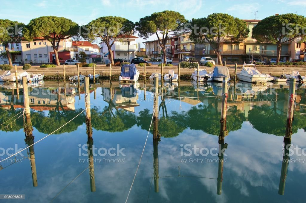 Canal and boats in Grado in bright morning light. Italy. stock photo