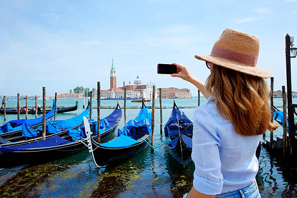 canal and gondolas with tourist eye - italien urlaubsziele stock-fotos und bilder