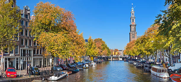 canal and westerkerk tower in amsterdam, the netherlands in autumn - westerkerk stockfoto's en -beelden