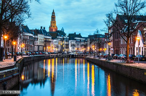 The photo is shot along a canal at night in Groningen with the Aa-Kerk church and historic center visible in the background. The street lights are reflected in the river. The sky is blue with copy space.