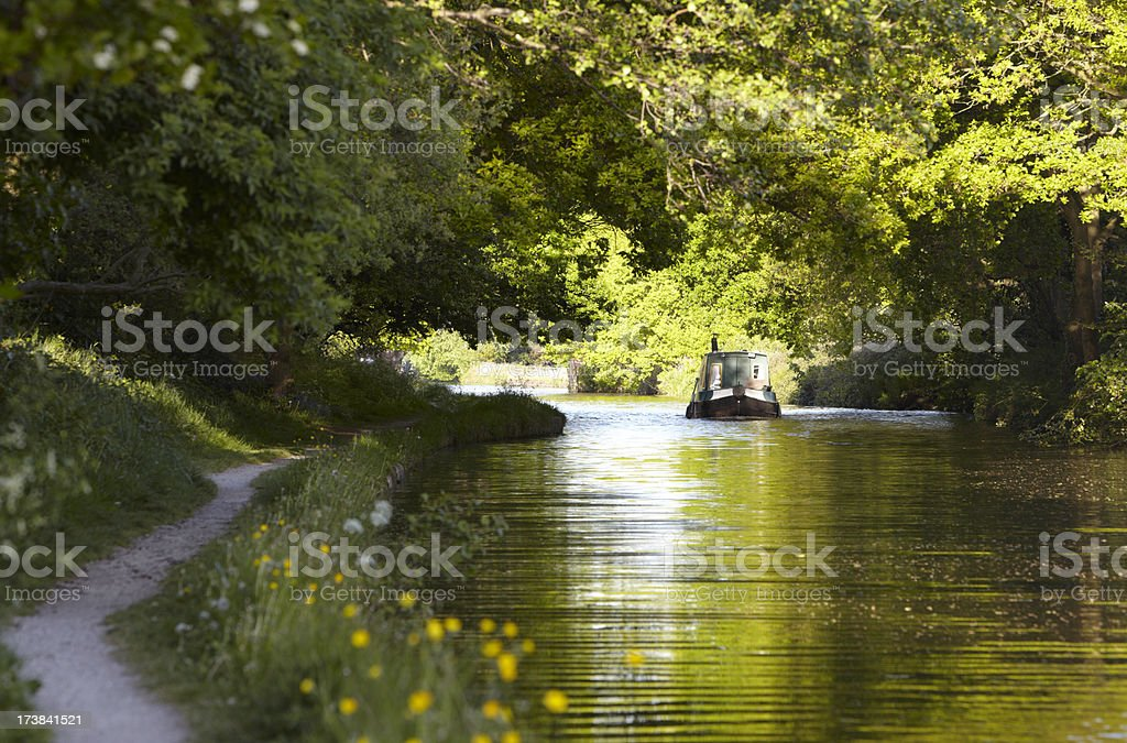 Canal barge moves through green summer dappled shade stock photo