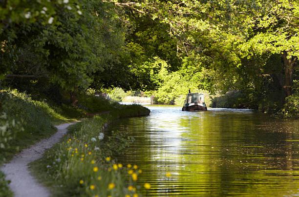 Canal barge moves through green summer dappled shade