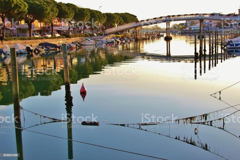 Canal, boats and pedestrian bridge in Grado, Italy. stock photo