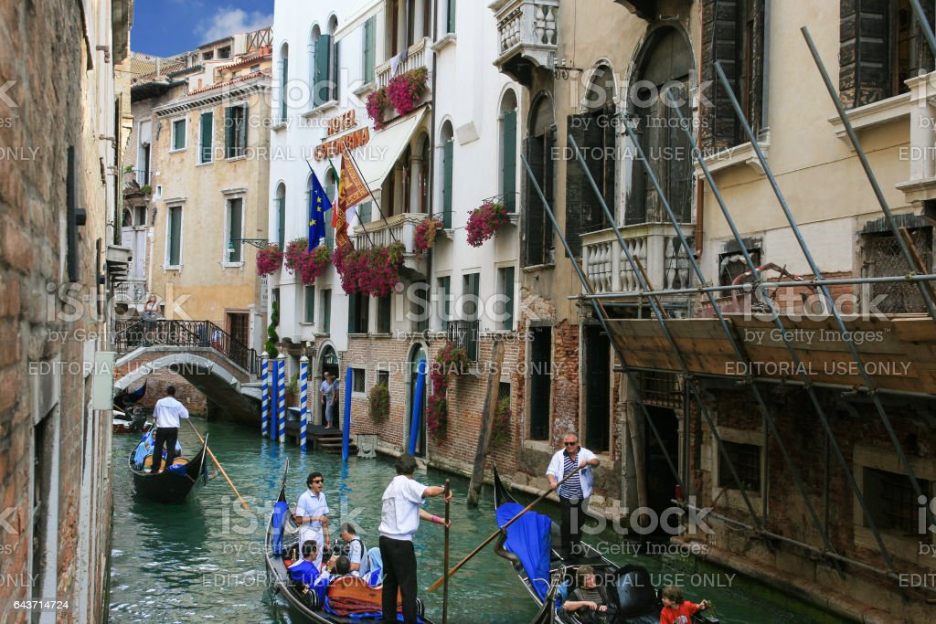 Canal, Gondolas, Tourists, and White Stucco Hotel, Venice, Italy. stock photo
