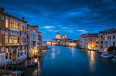 Classic view of famous Canal Grande with historic Basilica di Santa Maria della Salute in the background in beautiful mystic post sunset twilight with dramatic clouds in the sky at dusk, Venice, Italy