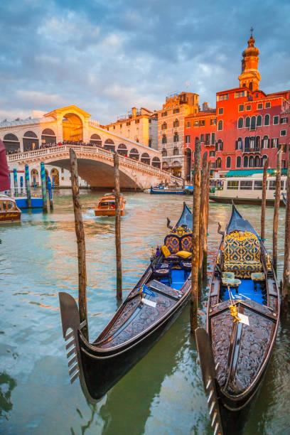 canal grande mit gondeln und rialto-brücke bei sonnenuntergang, venedig, italien - venezien stock-fotos und bilder