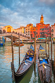 Classic panoramic view with traditional Gondolas on famous Canal Grande with famous Rialto Bridge in the background in beautiful golden evening light at sunset in summer, Venice, Italy