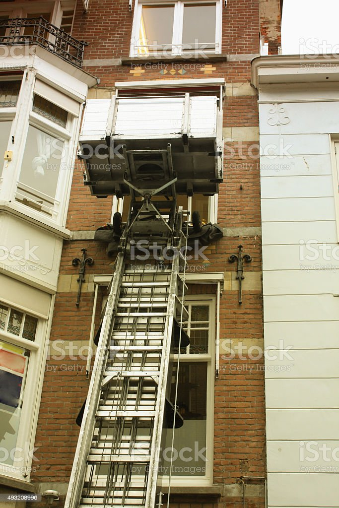 Canal house facade with a lifting machine in Holland. stock photo