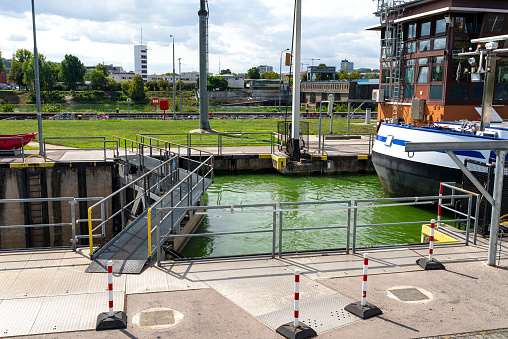 Canal lock with a barge waiting for the gate to open on the Moselle river in western Germany.