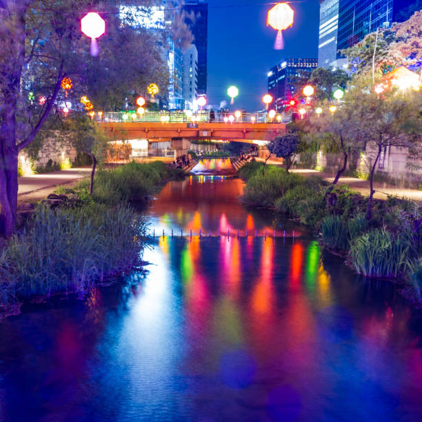 A canal of water flowing through a city reflecting bright colors on its surface stock photo