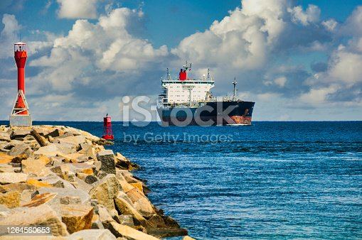 A large oil tanker sails past the Cape Cod Canal breakwater light as it enters the eastern end of the waterway as it travels from Boston down toward the Connecticut Coast.