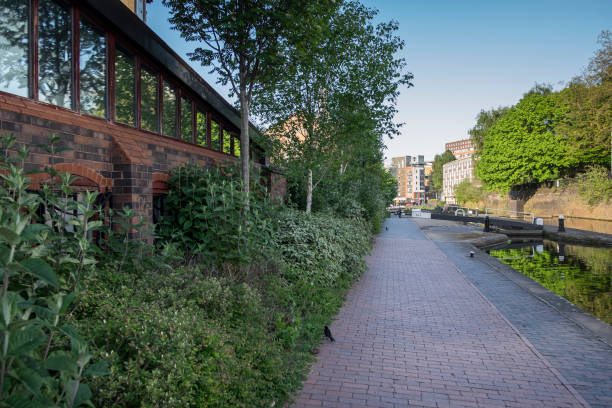 Canal path in Birmingham city centre, in the summer, with plentiful green foliage growing along the path stock photo