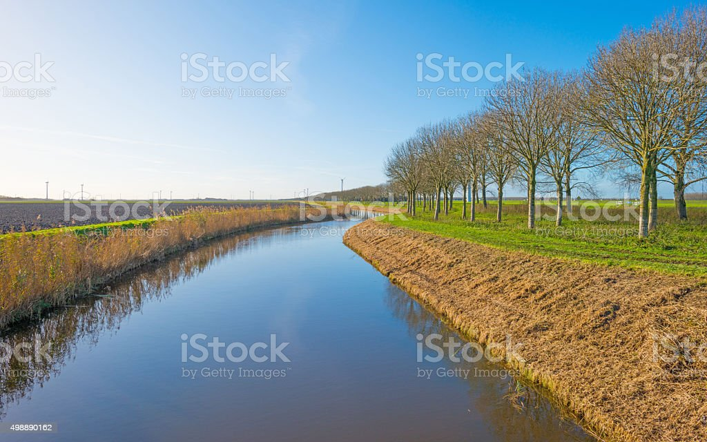 Canal through a rural landscape at sunrise stock photo
