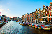 Amsterdam, Netherlands - April 5, 2018: Cityscape and canal boats at a canal in Amsterdam, Netherlands.