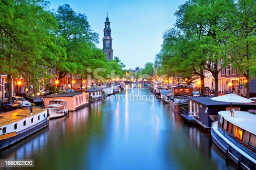 a canal with house boats in the city of Amsterdam at dusk
