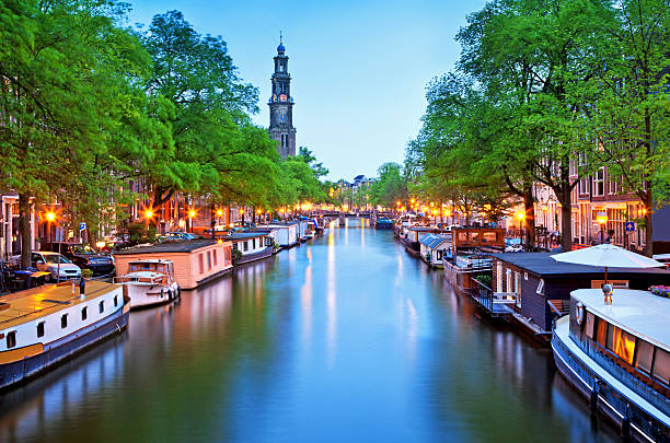Canal view of houseboats in Amsterdam a canal with house boats in the city of Amsterdam at dusk canal stock pictures, royalty-free photos & images